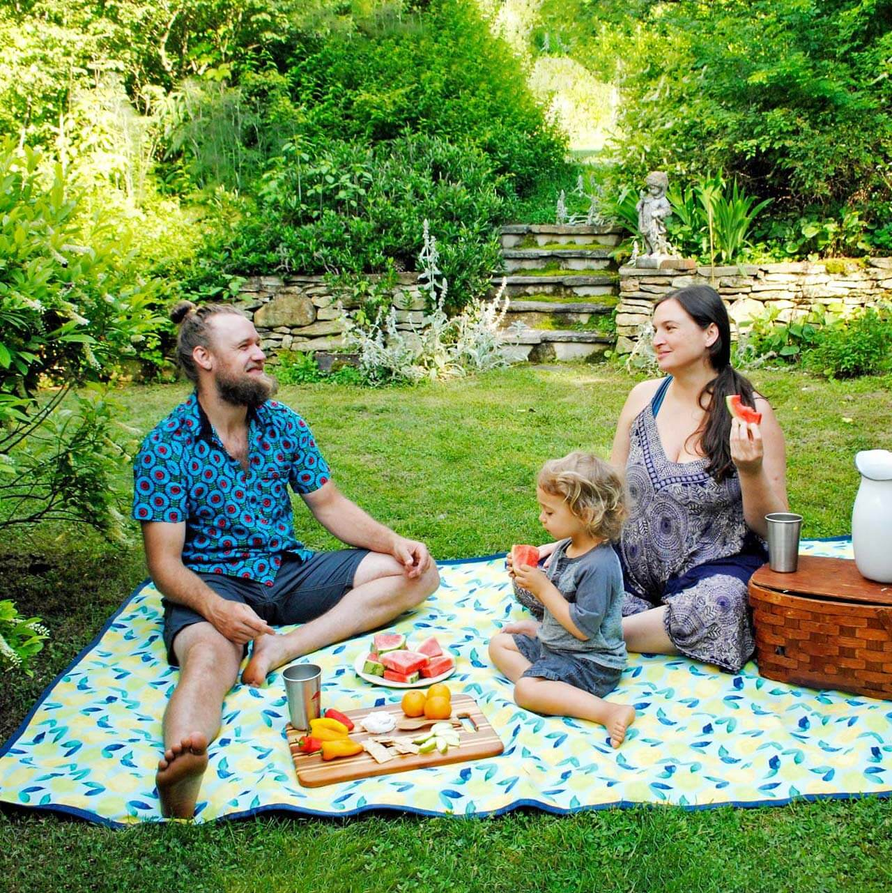 Family having picnic sitting on a Tarpestry.